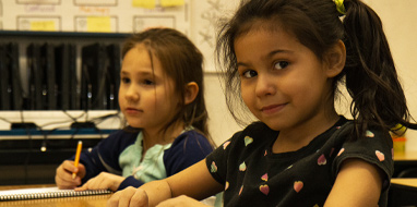 Two female third graders listen and write