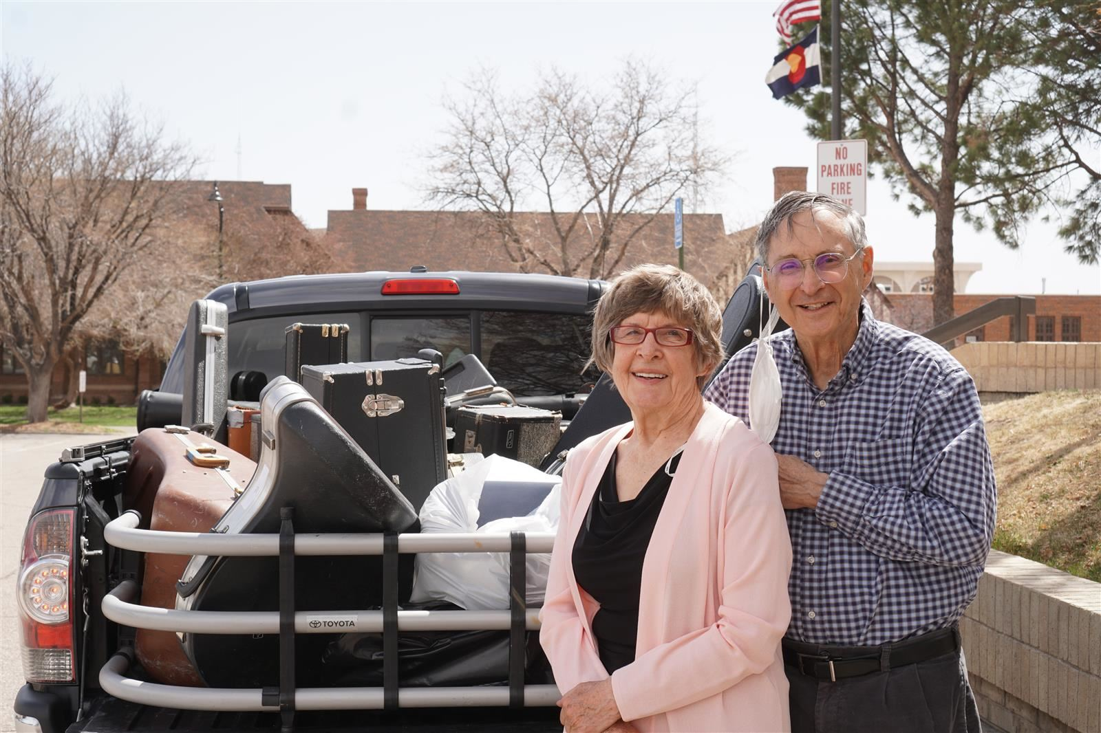Ricky and his Wife Dr. Dorothy DeNiro stand in front of a truck full of instruments they donated
