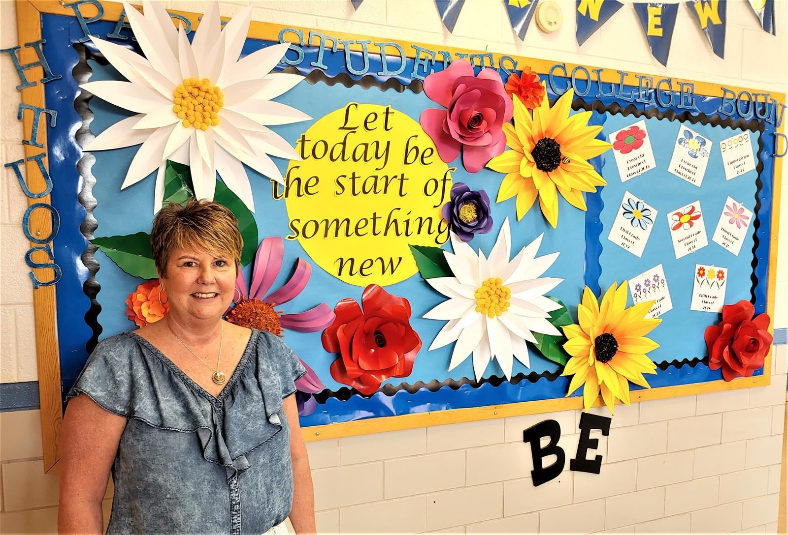 Principal Brunjack stands in front of a bulletin board decorated for spring.